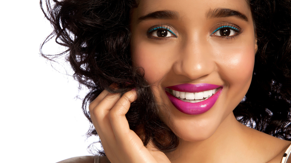 Young woman smiling against white background --- Image by © Camarena/Image Source/Corbis